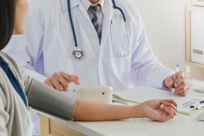 Doctor checking the blood pressure of woman patient
