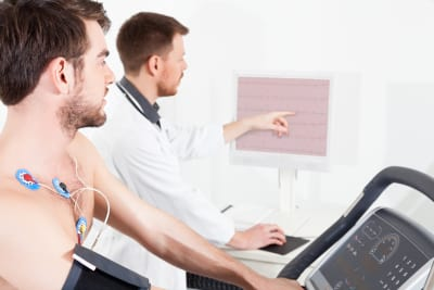 Doctor shows the patient the ECG recording of the electrical activity of the heart