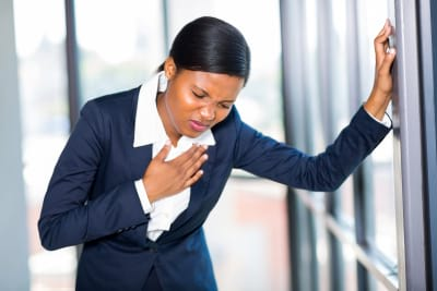 young african american businesswoman having heart attack or chest painc